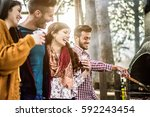 happy friends eating sausages... | Shutterstock . vector #592243454
