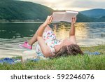 Young Woman Reading A Book By...