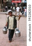 Small photo of KATHMANDU, NEPAL. 23 September 2008: The water carrier on the street of Kathmandu in the background of the Maoist slogan. Patan, Durbar Square, Nepal