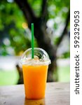 orange juice with ice cubes in... | Shutterstock . vector #592329053