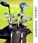 golf clubs in a bag with a course in the background - stock photo