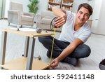 man assembling furniture at home | Shutterstock . vector #592411148