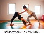 yoga instructor assisting... | Shutterstock . vector #592493363
