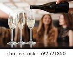 Man Fills Glasses Of Champagne...