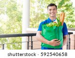 smiling delivery man holding... | Shutterstock . vector #592540658