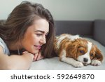 the girl with the puppy in bed. ...   Shutterstock . vector #592649870