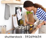 young woman in the kitchen... | Shutterstock . vector #592694654