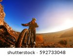 cyclist man standing on a hill... | Shutterstock . vector #592733048