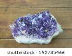 Amethyst geodes segment from Uruguay on a vintage wooden background