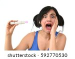 Small photo of young pregnant woman scared in shock checking pink positive result on pregnancy test surprised and stressed in accidental motherhood and unwanted baby isolated on white background