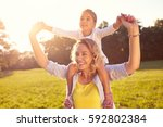 happy mom and female child on... | Shutterstock . vector #592802384