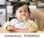 cute baby girl brushing her... | Shutterstock . vector #592838063