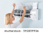 a young woman cleaning air... | Shutterstock . vector #592859936