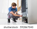young male serviceman working... | Shutterstock . vector #592867040