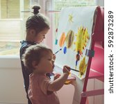 two little girls painting on... | Shutterstock . vector #592873289