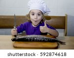 girl  to clean a live fish  joy ... | Shutterstock . vector #592874618