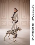 Stylish girl in a suit rider poses with Dalmatian. Creative colors
