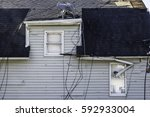 Small photo of NAPLATE, IL/USA - MARCH 3, 2017: Cables entangle a bent satellite dish and dangle over the roof and side of a house damaged by an EF-3 tornado that wreaked havoc across this small town on February 28.