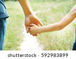 the parent holding the child's... | Shutterstock . vector #592983899