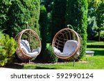 two hanging chairs in a garden... | Shutterstock . vector #592990124