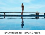girl near the swimming pool in... | Shutterstock . vector #593427896