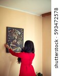 woman in red hanging the art... | Shutterstock . vector #593472578