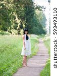 Small photo of Alice in Wonderland. Girl standing on the road in the forest