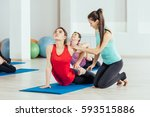 teacher helping with yoga pose... | Shutterstock . vector #593515886