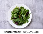 Small photo of Salad plate with mixed greens of arugula, mesclun, spinach on stone background. Healthy food. Top view
