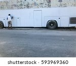 man painting bus in the garage | Shutterstock . vector #593969360