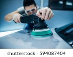 man doing a car polish with the ... | Shutterstock . vector #594087404