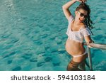 pregnant lady in the pool | Shutterstock . vector #594103184