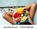 Small photo of Girl relaxing and eating fruit plate by the hotel pool. Exotic summer diet