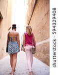 Small photo of Rear view of two teenager girls friends walking together in an old city street on holiday, with golden sun light, outdoors. Adolescent women with smart phone in pocket, travel recreation lifestyle.