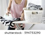 young woman ironing clothes on... | Shutterstock . vector #594753290