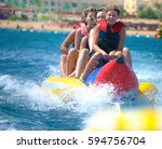 people ride on banana boat on... | Shutterstock . vector #594756704