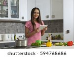 young woman cooking in the... | Shutterstock . vector #594768686