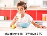 cute boy drinking milk at...   Shutterstock . vector #594826970