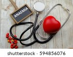Small photo of Word Anaemia written on blackboard with stethoscope, medicine and heart shape symbol on wooden background.
