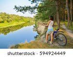 girl with a bicycle by the... | Shutterstock . vector #594924449