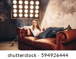 girl actress sits on the couch... | Shutterstock . vector #594926444