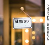 Small photo of WE ARE OPEN sign board through the glass of store window. Filtered image.