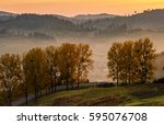 mountain rural area in autumn season. agricultural field in fog on a hill near the forest with red foliage. beautiful and vivid landscape. - stock photo