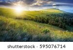 day and night time change. high mountain idyllic landscape. grassy meadow with forest on hillside. epic nature concept. - stock photo