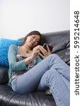 woman sitting on couch using... | Shutterstock . vector #595214648