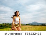 laughing young woman jumping in ... | Shutterstock . vector #595232438
