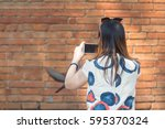 Woman Tourist is Taking Photo by Mobile Phone with Big Brick City Wall Background. Set as Copy Space for Text.