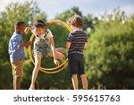 girl jumps thourgh hula hoop... | Shutterstock . vector #595615763