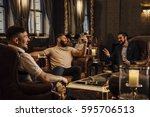 three men are enjoying drinks... | Shutterstock . vector #595706513