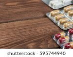 pills on grunge wooden table.... | Shutterstock . vector #595744940